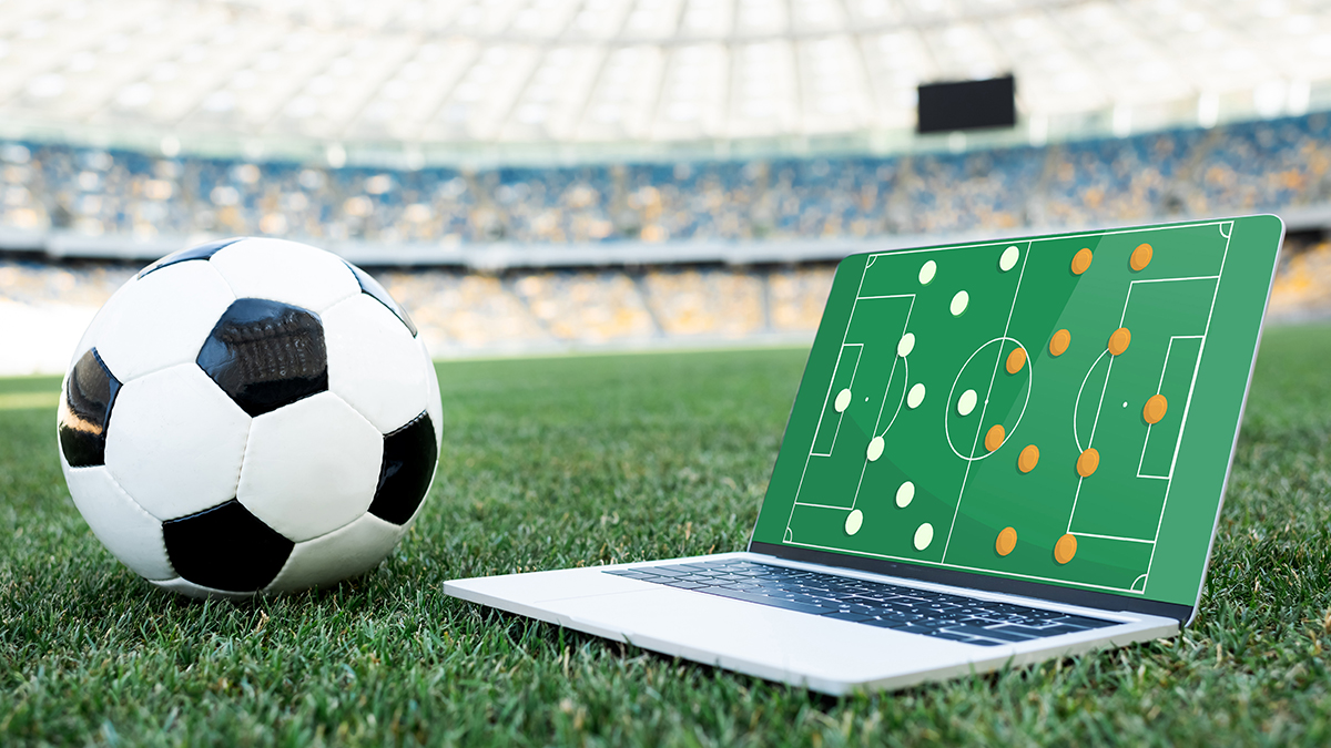 football and laptop on pitch