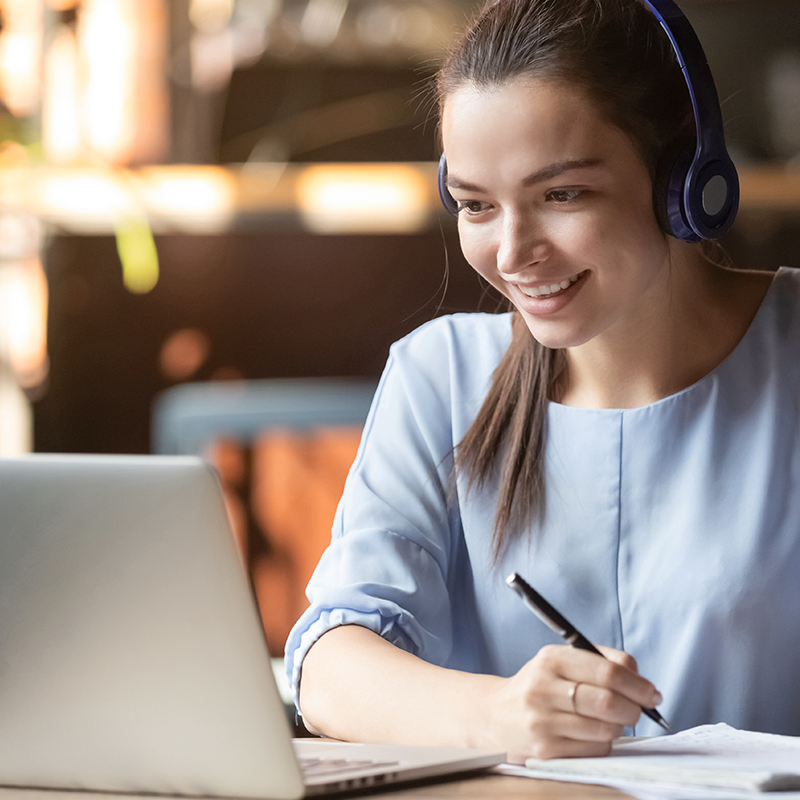 woman in front of laptop with headphones taking notes while smiling