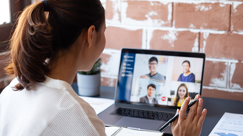 woman waving at colleagues on his laptop